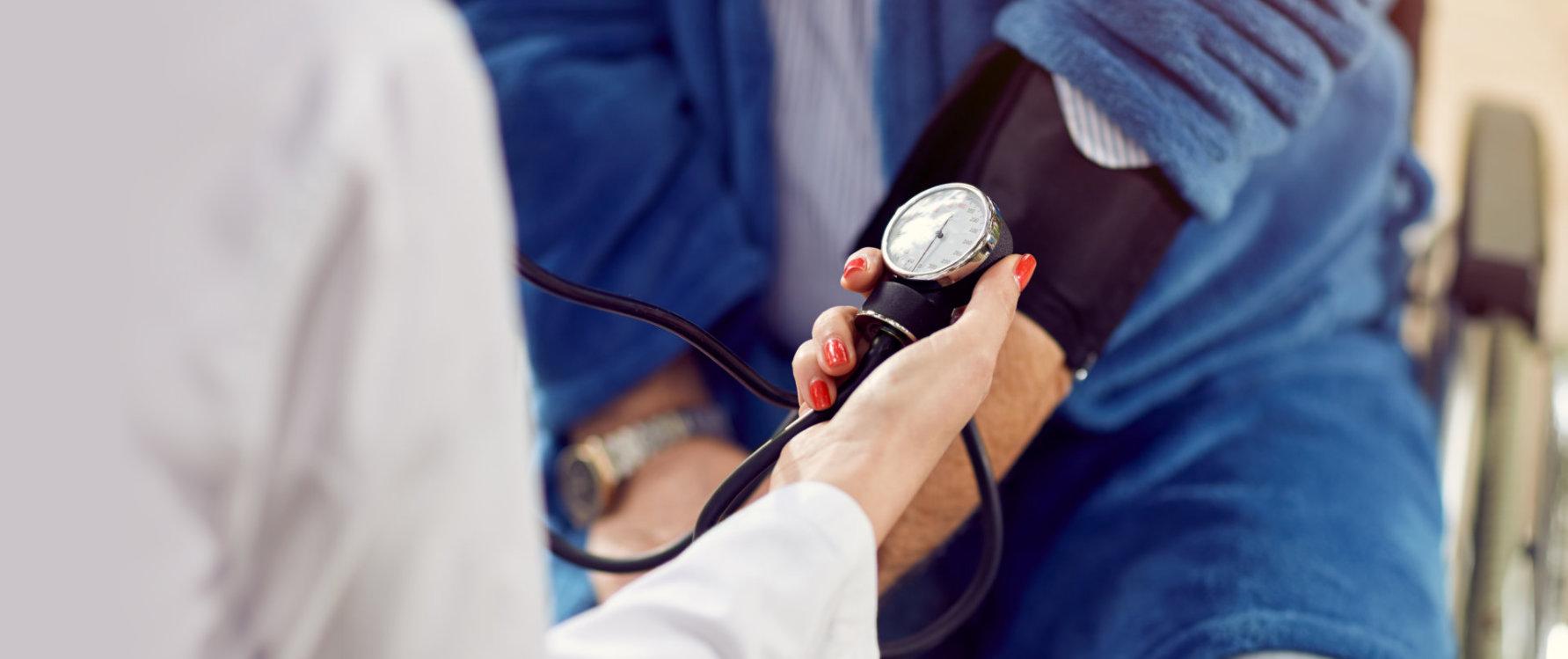 Close up checking the hypertension assessment of blood pressure elderly men in wheelchair