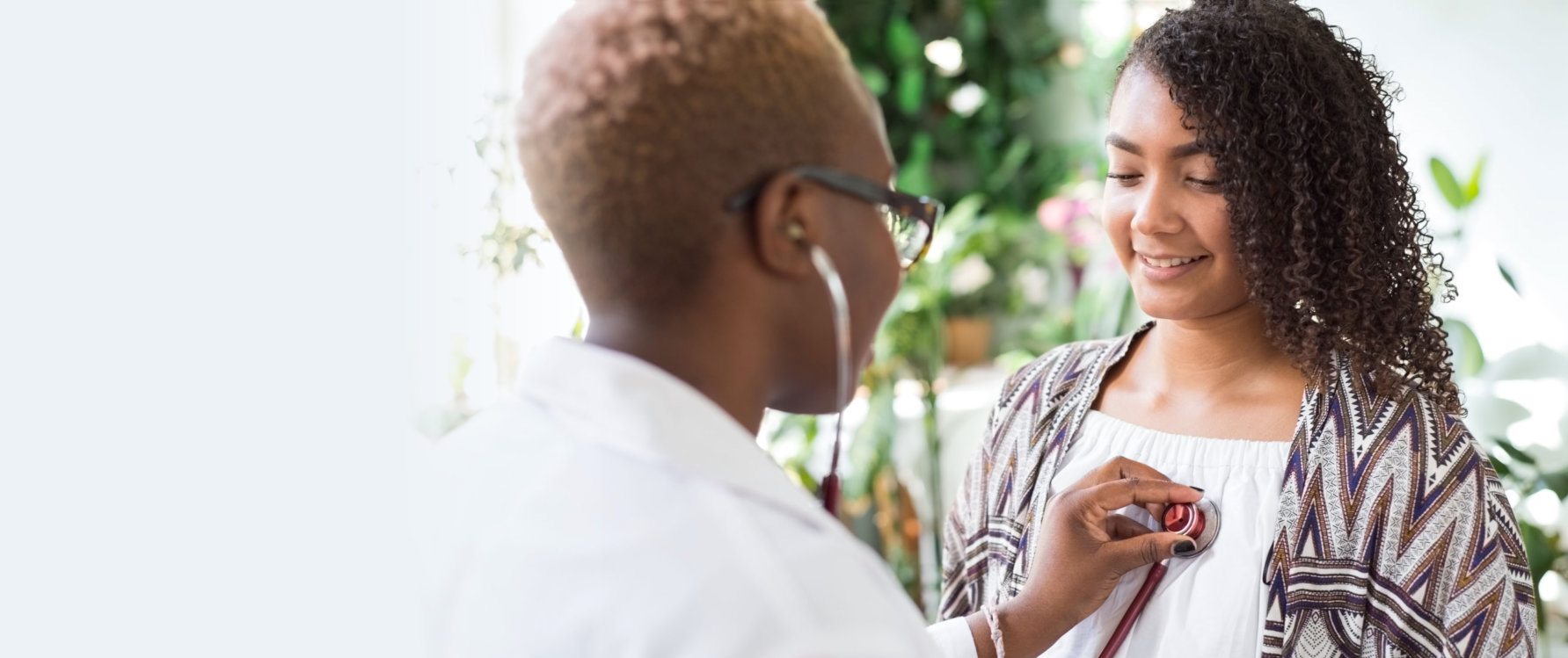 African American girl doctor using a stethoscope to conduct auscultation for a patient