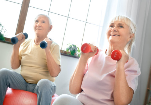 Senior men and women together indoors sitting on exercise ball doing aerobics holding dumbbells smiling