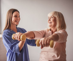 Beautiful old lady is doing exercises with dumbbells and smiling