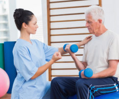 Female trainer assisting senior man in lifting dumbbells at gym