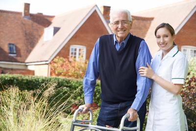 carer helps senior man to walk in garden using walking frame