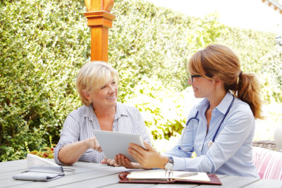 Elderly women sitting in the garden with home health care nurse and consulting